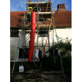 Carrying Micafil insulation up scaffolding ready to pour down around flue